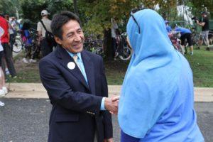 County Board member Walter Tejada talks to a resident outside Oakridge Elementary School