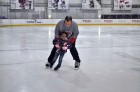 Washington Capitals Strength and Conditioning Coach Mark Nemish teaches a child to skate during Monumental Sports & Entertainment's holiday party