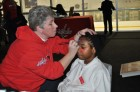 A child has his face painted with the Capitals logo during Monumental Sports & Entertainment's Family-to-Family holiday party at Kettler Capitals Iceplex