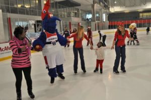 Washington Wizards mascot G-Wiz and Washington Capitals spirit squad members – Red Rockers – skate with a family at Kettler Capitals Iceplex