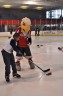 Washington Capitals mascot Slapshot instructs a child on stickhandling and shooting during Monumental Sports & Entertainment's Family-to-Family holiday party