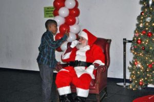 A child shares his holiday wish list with Santa during Monumental Sports and Entertainment's holiday party