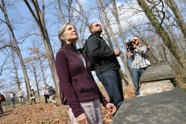Site visit attendees look at a portion of the woods set to be cleared