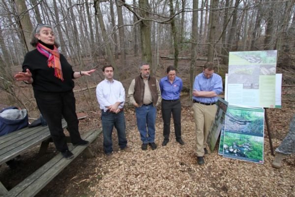 Cemetery and Army Corps of Engineers officials briefing attendees near a stream restoration site