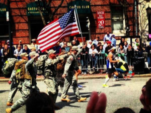 Albert Kim (to the right of the flag) running in the 2013 Boston Marathon