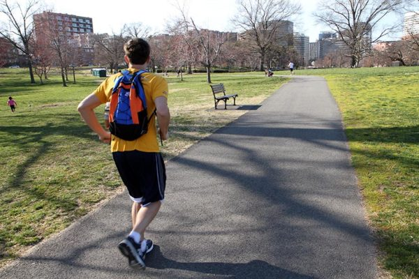 A man jogging through a park on a spring day