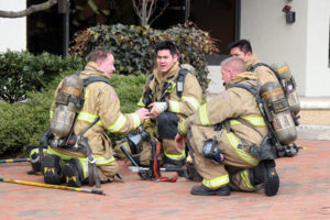 Firefighters gather during a Falls Church office fire