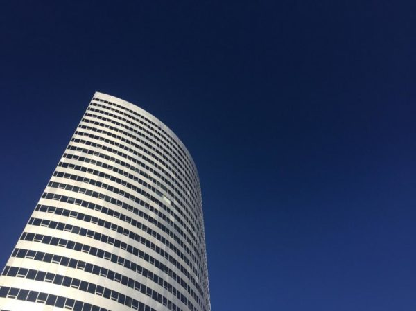 Office building in Rosslyn in front of a deep blue sky (Photo courtesy @jdsonder)