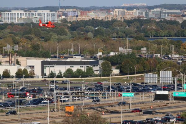 Coast Guard helicopter flies near I-395 and the Pentagon, with FedEx Field visible in the distance