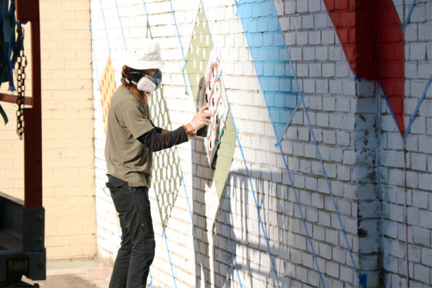 Artist Jason Woodside works on the new mural being painted in Rosslyn