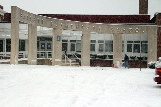 An Arlington Public Schools employee clears snow from in front of Barrett Elementary School