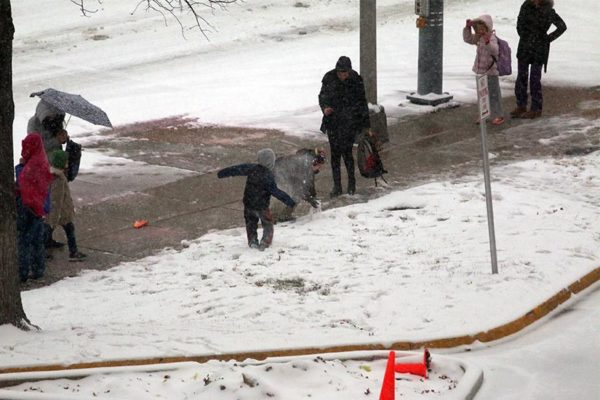 Children start a snowball fight while waiting for a school bus in Pentagon City