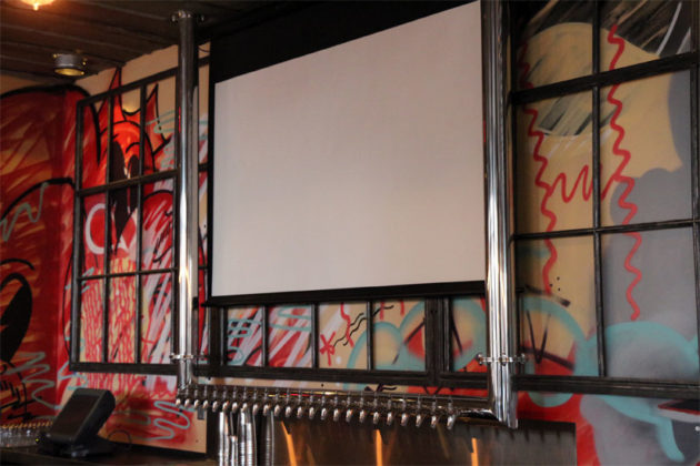 Projector screens retract behind the bar when the TV isn't on