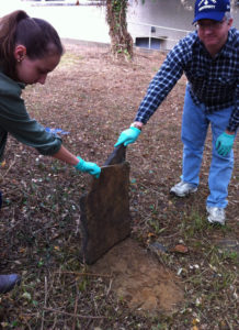 Dr. Patrick Mullins and student Emily Bielen carefully lift a fallen headstone (photo courtesy Marymount University