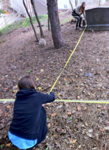 Morgane Murawiec, foreground, and the class peer mentor Kristen Eyler measure distances between headstones for a survey of the cemetery site (photo courtesy Marymount University)