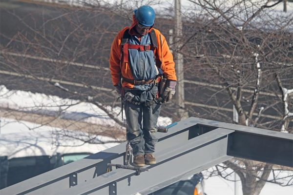 Construction worker stands on a beam