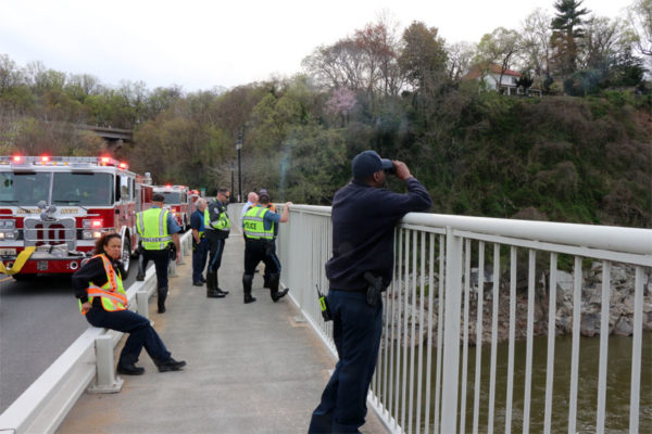 Emergency workers watch Arlington's technical rescue team rappel to the dead body
