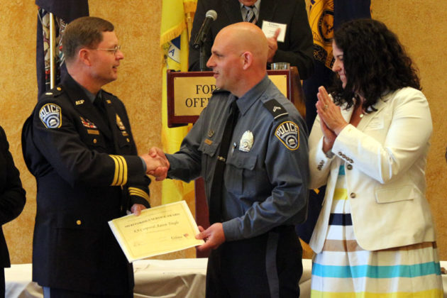 Cpl. Aaron Tingle receives the Meritorious Service Award from Acting ACPD Chief Jay Farr