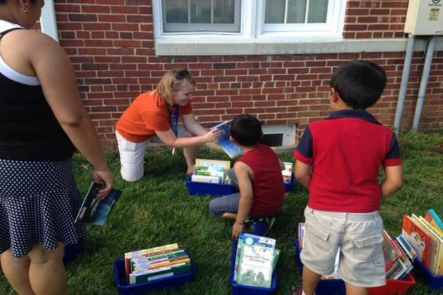 Barrett Elementary teacher Jen Flores helps students sift through the books  (courtesy photo)