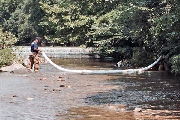 Firefighter placing a boom in Four Mile Run after a petroleum product was discovered in the water (photo courtesy ACFD)