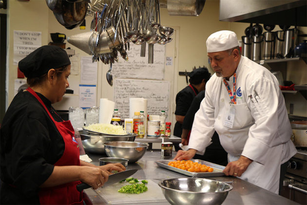 Chef instructor Alberto Vega prepares tomatoes.