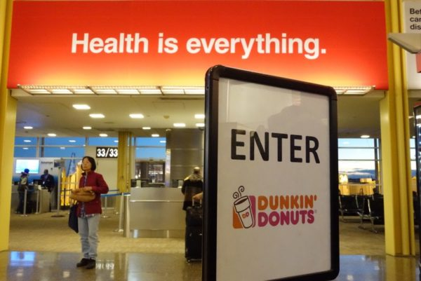 """Health is everything"" sign in front of Dunkin' Donuts sign at Reagan National Airport (Flickr pool photo by Kevin Wolf)"