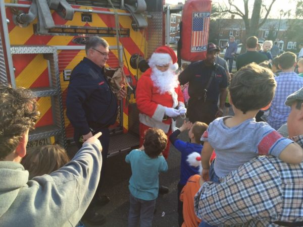 Children and parents gather around Santa and his fire truck in Fairlington