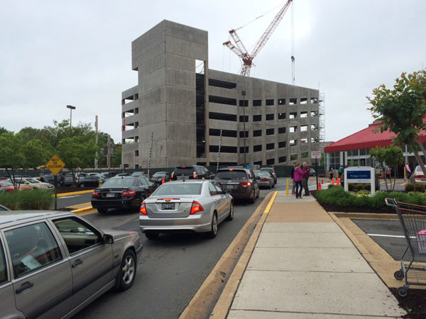 Under-construction parking garage rises above the busy Costco parking lot