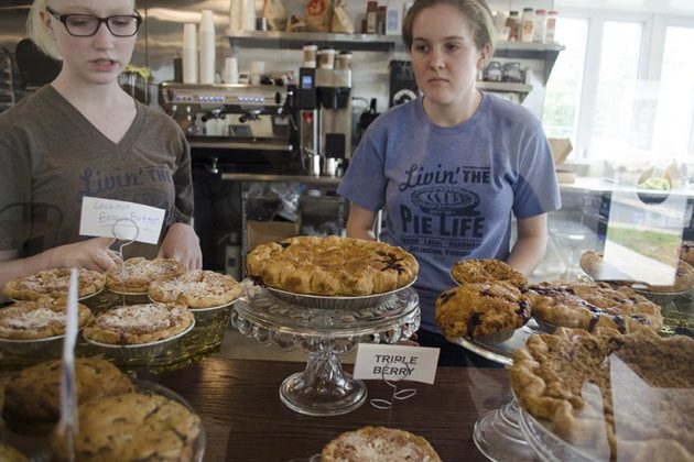 Employees explain various pie flavors to customers