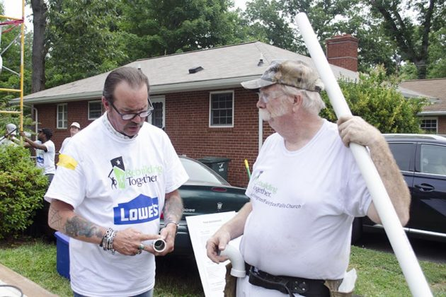Volunteers from Rebuilding Together and Lowe's discuss piping during the home repair