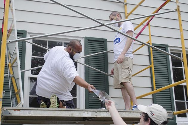 Volunteers from Rebuilding Together and Lowe's fix the home's  storm windows during the home repair