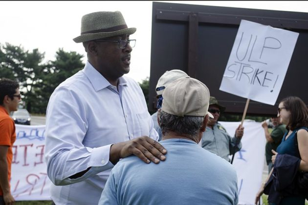 Christian Dorsey talks with a worker at the Arlington Cemetery Groundkeepers Strike