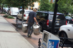 A man carries kegs away from the now-closed Hard Times Cafe in Clarendon
