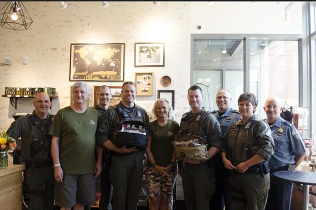 Owners of Olive Oil Boom pose with Arlington County Police Officers and the k9 Medical Kits