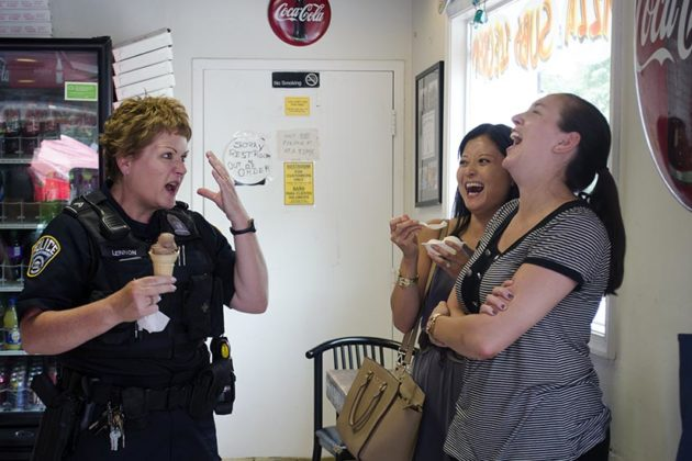An ACPD officer jokes with locals during the Cones With a Cop event