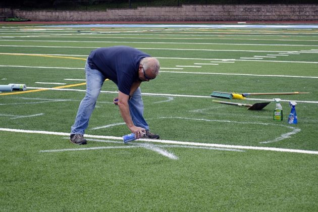 Arlington County workers clean up the vandalism that was on Yorktown High School's turf field