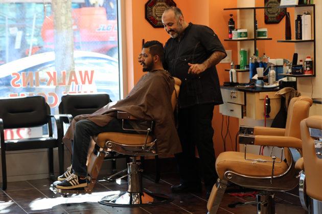 Habib Zaki cutting a customer's hair