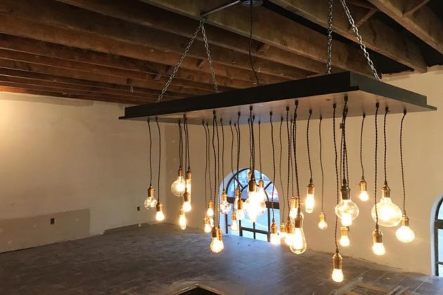 A light fixture hangs from the original rafters (photo via Facebook)