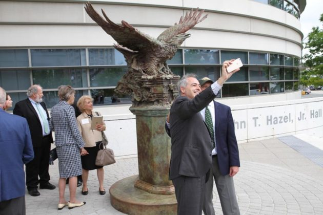 GMU president Angel Cabrera and law school dean Henry Butler take a selfie with the eagle