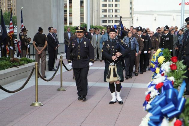A lone piper leads representatives of law enforcement agencies into the ceremony